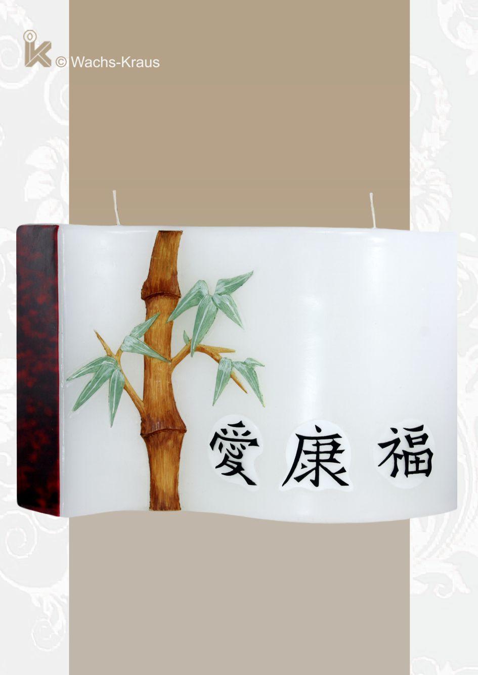 Die Kerze hat eine Wellen-Form. Verziert ist sie mit  aus Wachs gegossenen Bambus, den drei chinesischen Schriftzeichen für Liebe, Glück und Gesundheit.